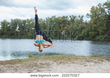 Girl is engaged in sports in nature. She makes somersaults