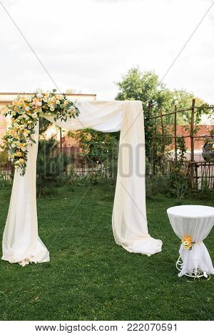 Open air decorated area for the wedding ceremony with a wooden arch decorated with fresh flowers and beige material. Beautiful wedding set up. Wedding ceremony on green lawn in the garden. Registration at the place of marriage.