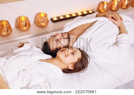 man and woman lying down on massage beds at Asian luxury spa and wellness center