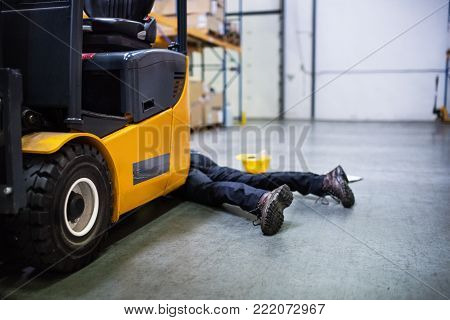 An accident in a warehouse. Unrecognizable man lying on the floor next to a forklift, unconscious.