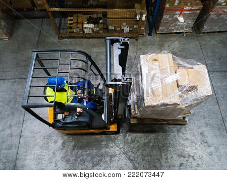 Man forklift driver working in a warehouse. Top view.