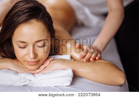Young beautiful relaxing woman getting spa massage of shoulder in beauty salon