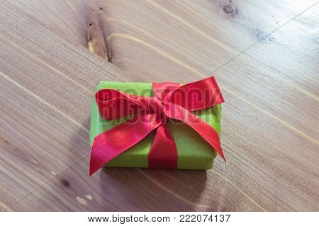 Small gift box wrapped in green paper with a large red satin bow, centered, neutral wood background, copy space, horizontal aspect