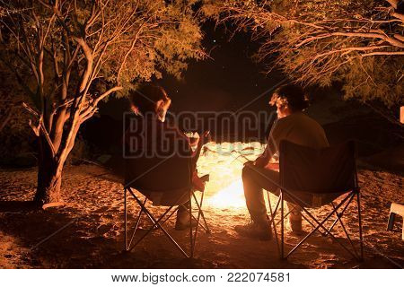 Couple sitting at burning camp fire in the night. Camping in the forest under starry sky, Namibia, Africa. Summer adventures and exploration in the african National Parks. Selective focus on fire.