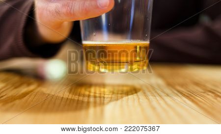 Image of man with glass of beer on table in cafe