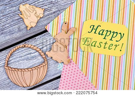 Cut out plywood Easter figures and greeting card. Colorful patterned sheets of paper for craft. Carved wooden Easter rabbits and basket on rustic wooden background. Happy Easter concept.
