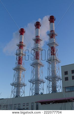 Industrial pipe thermal power station white with red from the smoke in the blue sky. ecology conceptual