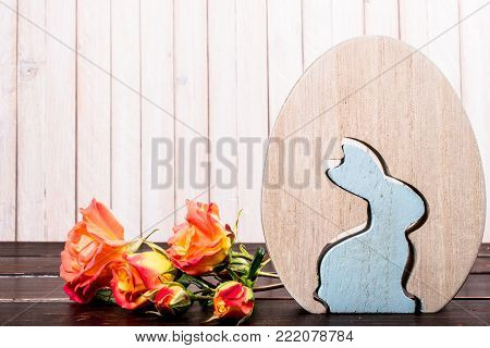 close-up of wooden easter egg and easter rabbit with rose flowers on wooden background. template with copy space. easter concept and easter greeting card.