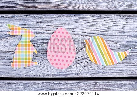 Paper cutouts for Easter holidays. Papercut patterned figures of Easter rabbit, egg and bird on rustic wooden background. Paper handmade cutouts for Easter.