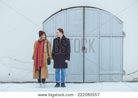 Stylish couple in classic suite standing near white historical building. Fashionable winter clothing.