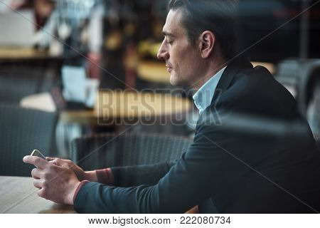 Side view serene man looking at monitor of phone while sitting at desk in confectionary concept. Technology and relax concept