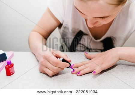 Girl paints nails, gel purple, gel nail manicure. Saw, primer gel. Manicure arms. Nail Care.