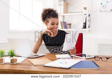Paperwork. Happy smiling business woman in formal wear sitting at wooden desk in modern office and reading report document.