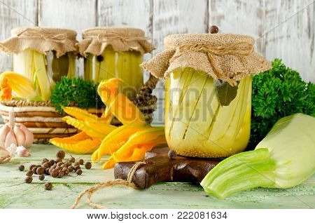 Zucchini preserve in glass jar on a wooden table. Homemade canning winter preserve