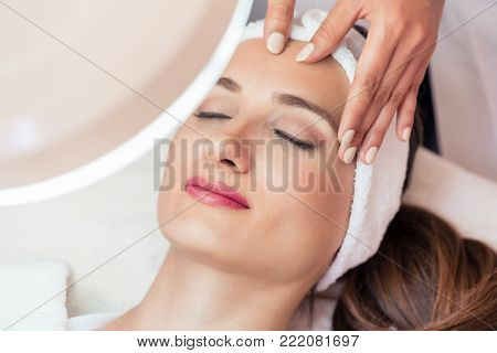 High-angle view of the face of a relaxed woman smiling under the benefits of anti-aging facial massage in a contemporary beauty center