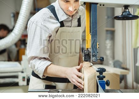Man holding timber on band saw machine. Board with working assignments hanging on wall near machine-tool. Young man dressed in white checkered shirt and overalls.