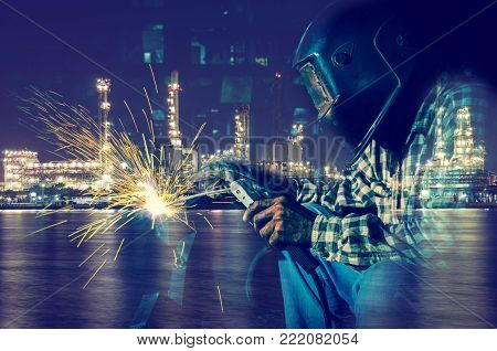 welder at work with Oil and gas refinery - Petrochemical factory background