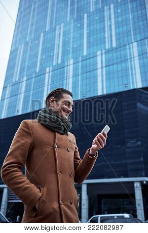 side view beaming man sending message by phone while walking on street. Gadget concept