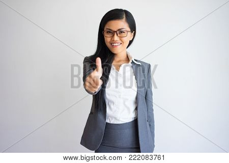 Closeup portrait of smiling young pretty Asian business woman looking at camera and showing thumb up. Recommendation concept. Isolated front view on grey background.