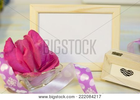 The concept of Love, Wedding, Proposal, Anniversary, St. Valentine's Day with a wooden photo frame, a wooden casket and a bowl with pink rose petals on a light wooden table