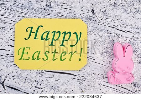 Easter greeting card and silicone mold. Yellow Easter greeting card and pink rabbit shaped silicone mold for baking. Preparations for Easter holidays.