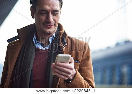 Outgoing male typing in mobile while situating outside. Technology concept