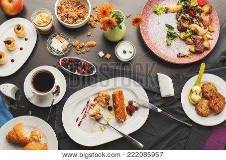 Eating sweet restaurant breakfast with oatmeal cookies, croissants, yogurt, cheese pancakes, muesli, fresh berries and freshly brewed tea served on black table. Nourishing morning meals, top view