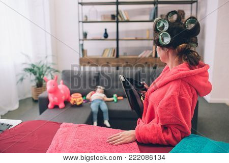 mother and baby together engaged in housework Ironing clothes . Housewife and kid doing homework. Woman with little child in the living room. Homemaker doing many tasks while looks after her infant.