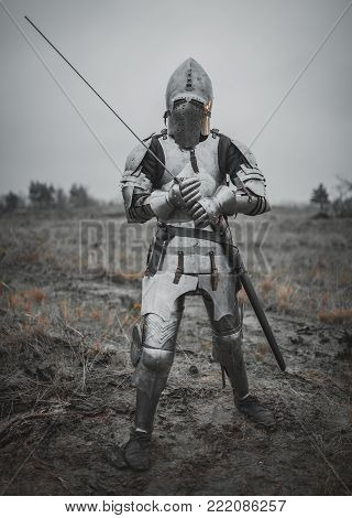 Girl in image of Jeanne d'Arc goes on meadow across mud in armor and helmet with closed visor and sword in her hands.