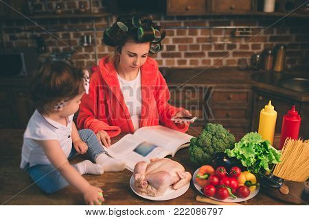 Mum at home. Young mother with little child in the home kitchen. Woman doing many tasks while looks after her baby. She is reading a glossy magazine and looking for delicious recipes.