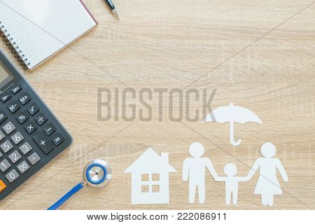 Top view of insurance concept with family paper, stethoscope, house paper, umbrella paper, calculator and notepad
