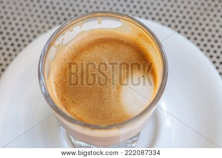 Top view cortado coffee froth, consumed from