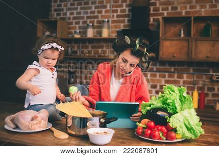 Mum at home. Young mother with little child in the home kitchen. Woman doing many tasks while looks after her baby. Use a tablet PC. Technology and Maternity