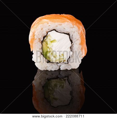 Sushi roll with fish, vegetables and cheese. Traditional japanese food on black glass with reflection, copy space. Asian restaurant meals delivery