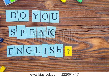 Learning Foreign Languages concept: Do you speak English inscription on blue paper on a rustic wooden background, top view