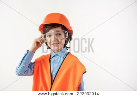 Portrait of smiling little boy trying himself as a construction manager. He is wearing safety glasses. Copy space in right side. Isolated on background