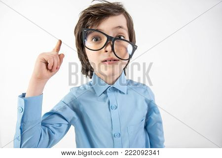 That is it. Portrait of uncombed kid with glasses aslant dreaming of making scientific breakthrough. He is holding finger up. Isolated on background