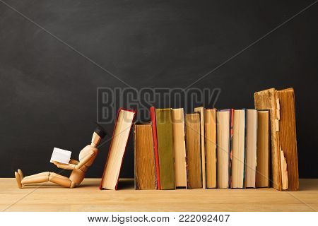 Educational background. Wooden marionette in graduation hat sitting near books and reading against empty classroom blackboard for copy space. Back to school concept
