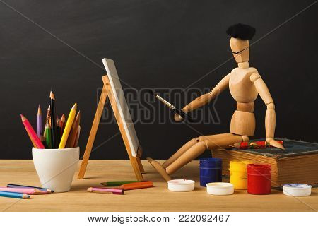 Art background. Wooden marionette in hat sitting on old book and painting against empty classroom blackboard. Back to school concept