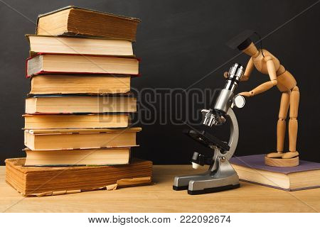 Educational background. Wooden marionette in graduation hat looking in microscope while standing near books pile against empty classroom blackboard for copy space. Back to school concept
