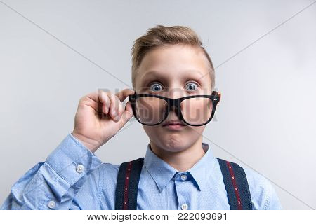 Portrait of well dressed kid taking off spectacles. His eyes are wide open with surprise. Isolated on background