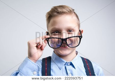 Portrait of intelligent child wearing glasses and looking with joy. Isolated on background