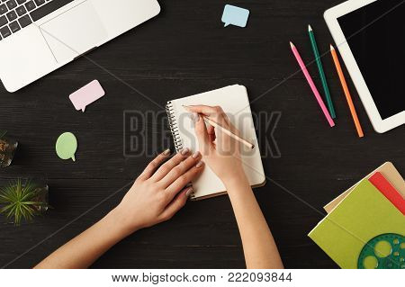 Woman's hands writing in notebook. Top view of human hands, laptop keyboard, notebook, digital tablet and pencils on a wooden table background. Education, business, technology concept