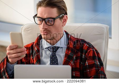 Portrait of serious man sitting in armchair. He is looking at mobile phone with intent look
