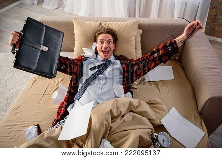 Happy adult male lying in bed and rejoicing. He is looking at camera with triumphant glance. Free from work concept