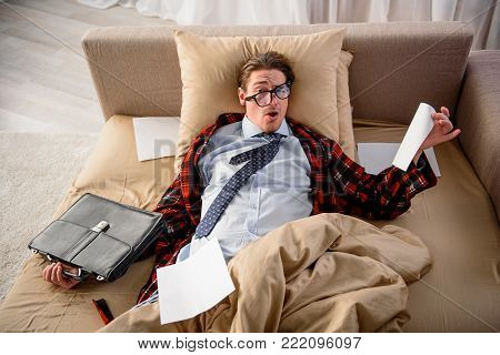 Shocked adult male lying in bed and holding briefcase and sheet of paper. He is looking at camera with weary look