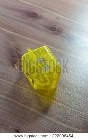 Yellow translucent plastic Hanukkah dreidel on a wood table, Hebrew letter Gimel facing up, copy space, vertical aspect