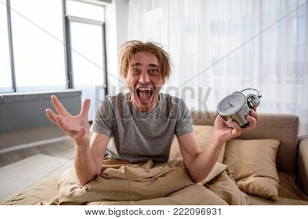 Waist up portrait of stressed man sitting in bed in the morning. He is looking at camera with mad look and holding the alarm at home