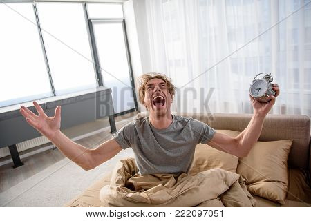 Furious guy sitting on bed with angry expression and holding the alarm clock in hand. He is screaming and looking up