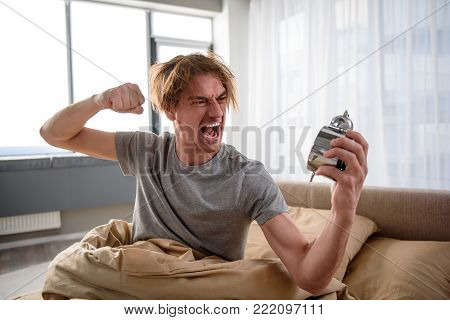 Feeling furious. Waist up portrait of angry guy sitting in bed in the morning. He is waving his hand at the alarm clock